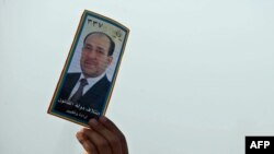 A man holds up a portrait of Prime Minister Nuri al-Maliki during a speech in Karbala ahead of the voting.