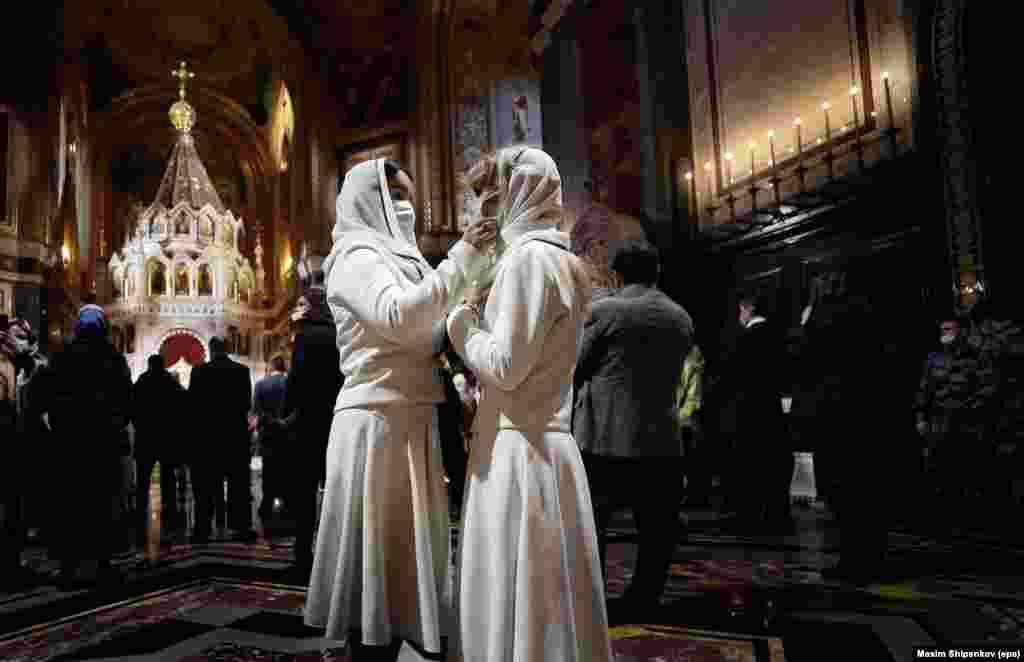 Верующие Русской православной церкви поправляют маски в храме Христа Спасителя в Москве