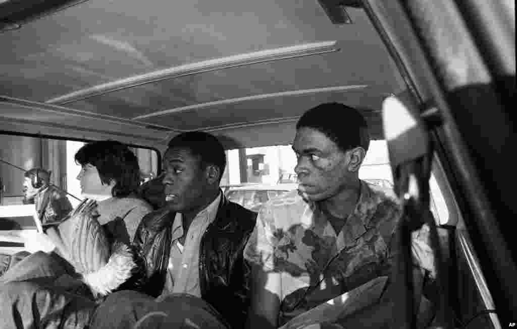 Троє заручників, яких відпустили з американського посольства 19 листопада 1979 року, в машині після пресконференції по дорозі на летовище. Зліва направо: Кеті Гросс, 22 роки, Пенсільванія; морський піхотинець сержант Лейделл Мейплз, 23 роки, Арканзас; морський піхотинець сержант Вільям Куарлес, 23 роки, Вашингтон
