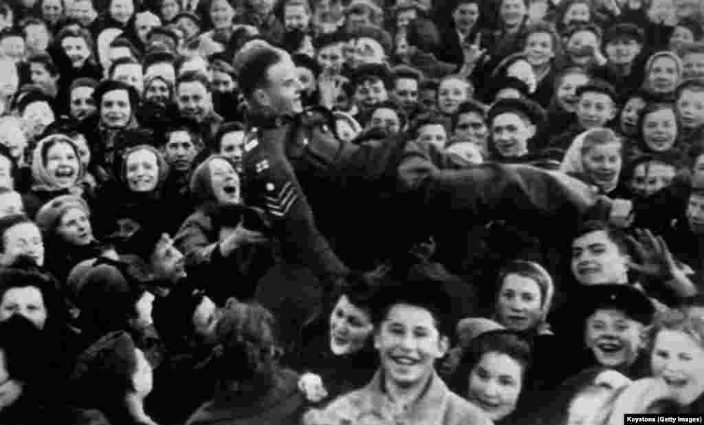 A British sergeant being thrown into the air by a crowd of youngsters in Moscow. The Soviet Union celebrated one day after most Allied countries because Germany's high command signed a second surrender document, as demanded by Josef Stalin, late on May 8. Due to time-zone differences, the signing in Berlin took place in the small hours of the following morning in Moscow.