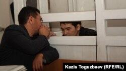 Адвокат Жандос Бұлқайыров (сол жақта) айыпталушы Саян Хайыровпен сөйлесіп отыр. Алматы, 17 қазан 2013 жыл.