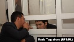 Адвокат Жандос Булхайыров (слева) общается с подсудимым Саяном Хайров в Алмалинском районном суде. Алматы, 17 октября 2013 года.