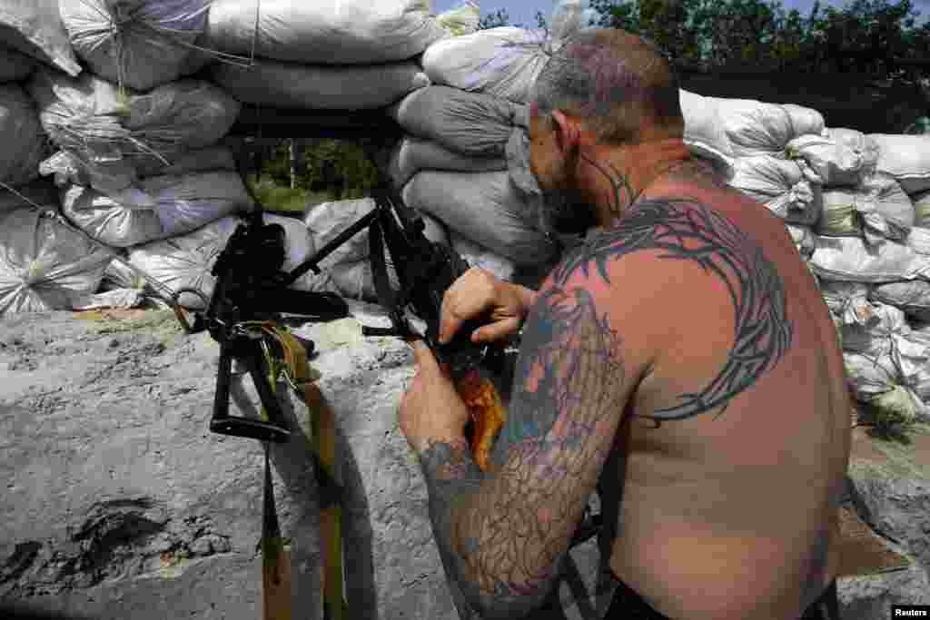 A pro-Russian militant mans a machinegun at front-line rebel position on the outskirts of the eastern Ukrainian town of Slovyansk on May 19. (Reuters/Yannis Behrakis)