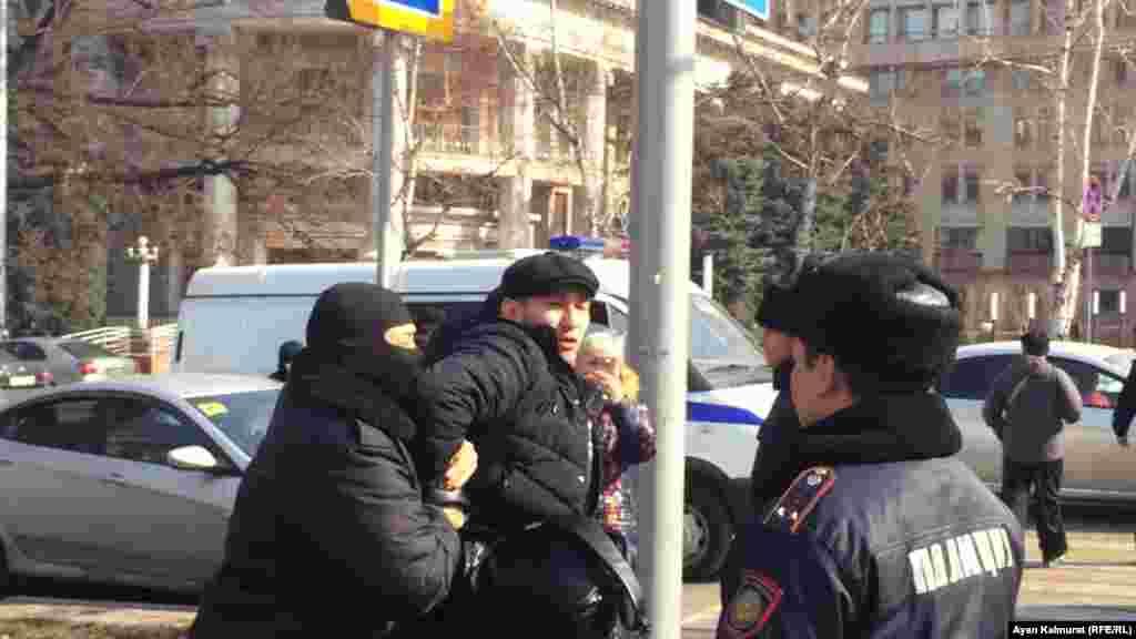 Полиция азаматтарды көліктеріне апара жатыр.
