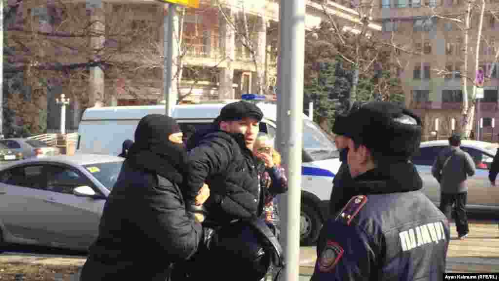 Полицейские ведут задержанного мужчину.