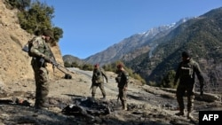 FILE: Afghan security personnel patrol during an ongoing antiterrorism operation in Dangam district near the Pakistan-Afghanistan border in eastern Kunar province.