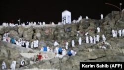 Muslim pilgrims walk and pray on Mount Arafat on August 30.