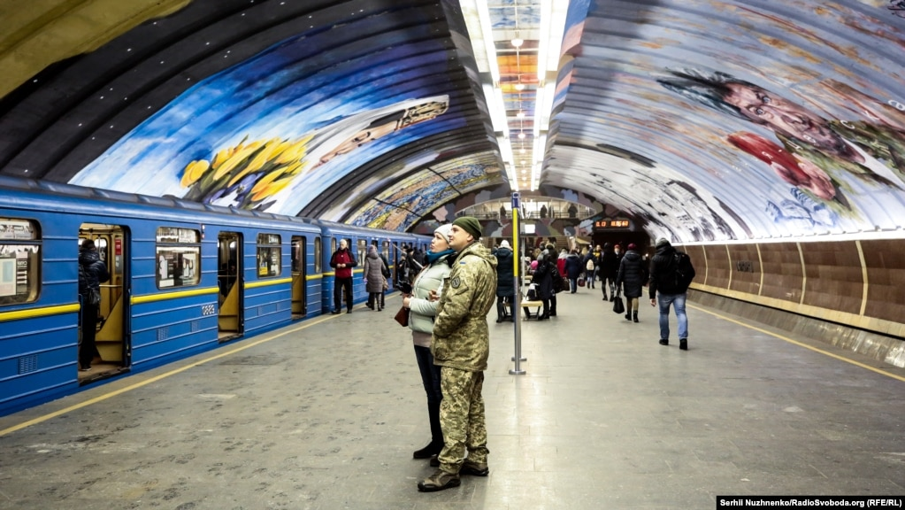 "A soldier and his wife take a moment to check out the art. A state official said the project, which cost 3.65 million hryvnia (about $132,000), was aimed at putting Kyiv on the art map. ""Today street art is [a reason] people come to New York or London; we would like Kyiv to be such a tourist city as well."""