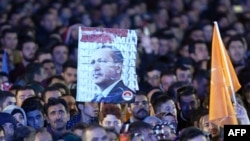 Supporters of the Justice and Development Party (AKP) hold a banner of Turkish President Recep Tayyip Erdogan during a speech by Prime Minister Ahmet Davutoglu at AKP headquarters in Ankara, on November 2.