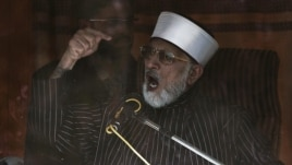 Qadri addresses supporters from behind bulletproof glass in Islamabad.