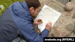 Мастак Яўген Анішчанка падфарбоўвае надпіс на шыльдзе