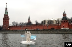 Wearing a polar bear costume, a Greenpeace activist takes part in a protest on the Moskva River in front of the Kremlin in Moscow on April 1 to draw attention to the consequences of Arctic oil drilling..