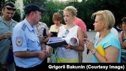 Полицейские составляют протокол об административном правонарушении на гражданскую активистку Анастасию Шевченко