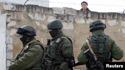 Український солдат дивиться на російських військових біля частини в Перевальному поблизу Сімферополя, 6 березня 2014 року