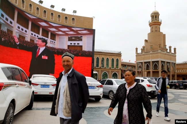 Ethnic Uyghur people walk in front of a giant screen with a picture of Chinese President Xi Jinping in the main city square in Kashgar in Xinjiang Uighur Autonomous Region, China September 6, 2018. The screen broadcasts a slideshow of images of Xi on loop