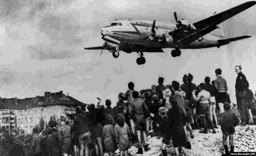 A U.S. Air Force C-54 Skymaster descends into Berlin's Tempelhof Air Base as hopeful Berliners watch on August 10, 1948. The airlift was in operation for 15 months after the Soviet authorities cut off the city. Some 101 participants died, including 40 Britons and 31 Americans, mostly due to nonflying accidents.