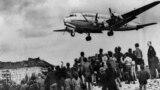 Un avion american de tic C-54 Skymaster în curs de aterizare la Baza militară aeriană Tempelhof de la Berlin, în timp ce berlinezii privesc cu speranță la 10 august 1948. Podul aerian a funcționat timp de 15 luni după ce sovieticii au blocat orașul. Circa 101 dintre participanții la operațiune au murit, între care 40 de britanici și 31 de americani, în cea mai mare parte a lor datorită unor accidente nelegate de zbor.