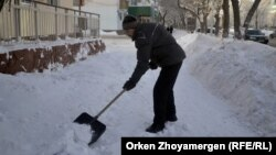 Дворник расчищает тротуар после снегопада в Астане. Иллюстративное фото.
