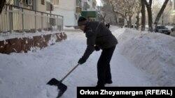 Дворник очищает тротуар от снега в Астане. Иллюстративное фото.