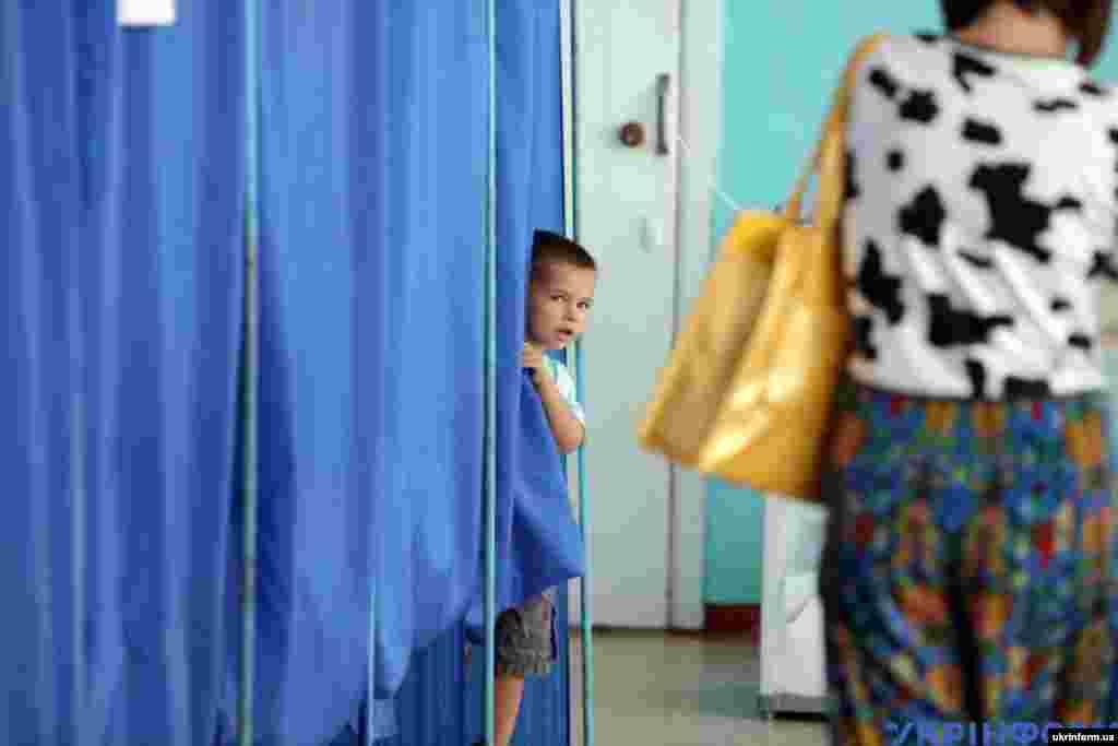 Хлопчик виглядає з кабінки для голосування у Харкові