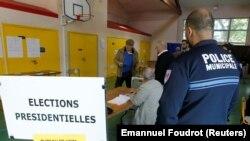 Полицейский наблюдает, как проходит первый тур президентских выборов во Франции
