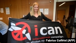 SWITZERLAND -- Nuclear disarmament group ICAN executive director Beatrice Fihn holds a banner with their logo after ICAN won the Nobel Peace Prize for its decade-long campaign to rid the world of the atomic bomb as nuclear-fuelled crises swirl over North