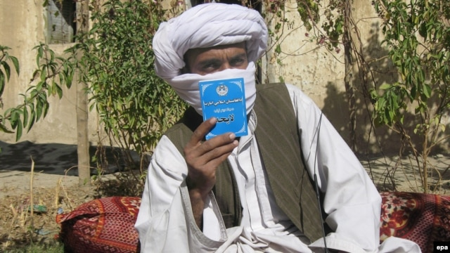 Mullah Wakeel, a Taliban leader, show a copy of the Afghan Taliban's code of conduct. Scholars say the Taliban has no authority to enforce Islamic law.