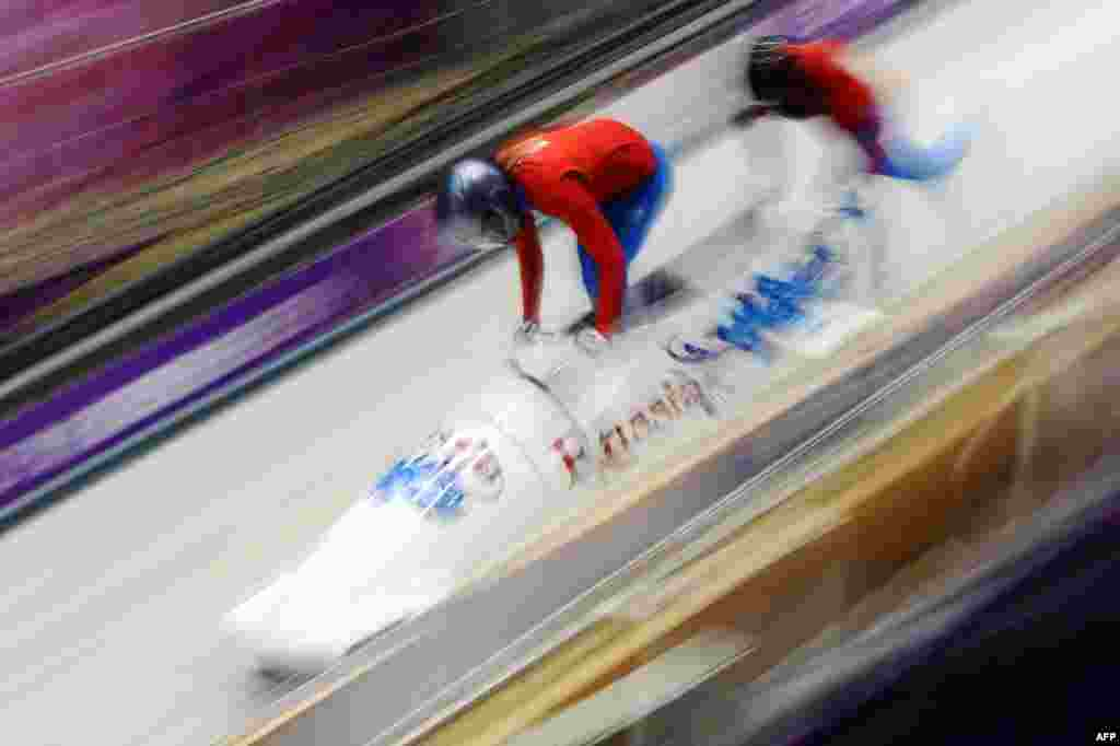 A Russian two-woman bobsleigh steered by Nadezhda Sergeyeva takes a practice run during a training session at the Sanki Sliding Center. (AFP/Lionel Bonaventure)