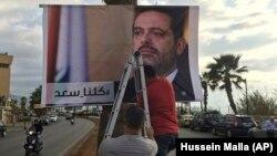 حامیان سعد حریری در حال نصب بنری در یکی از خیابانهای بیروت که بر روی آن ذکر شده «همه ما سعد هستیم».