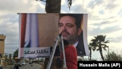 "Workers hang a poster of Prime Minister Saad Hariri with Arabic words that read, ""We are all Saad"" on November 9."
