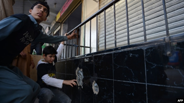 Pakistani children point to bullet holes at the spot where Nasiruddin Haqqani, a senior leader of the feared militant Haqqani network, was assassinated outside an Afghan bakery in the Bhara Kahu district on the outskirts of Islamabad on November 10.