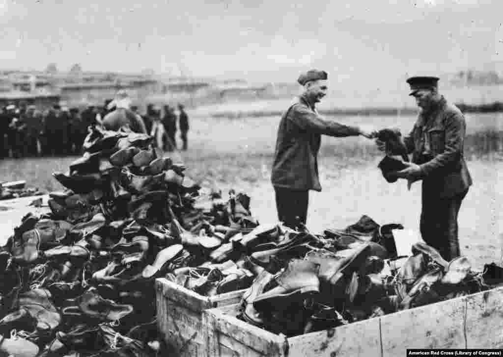 """Vojnik Sjedinjenih Američkih Država daje čizme ruskim vojnicima oslobođenim iz nemačkih logora za ratne zarobljenike. Razlozi zbog kojih je Amerika slala pomoć revolucionarnoj Rusiji bili su: """"prvo, obezbediti ono najneophodnije za ljude; drugo, značajno poboljšati šanse da Rusija ostane da se bori u Prvom svetskom ratu; treće, to je najefikasniji oblik američke propagande koji se mogao osmisliti""""."""