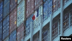 A French flag flies next to containers on a cargo ship owned by shipping company CMA CGM.