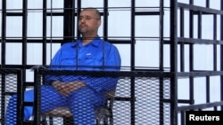 Saif al-Islam Qaddafi, the second son of Libya's late dictator Muammar Qaddafi, attends a hearing behind bars in a courtroom in Zintan, Libya, in 2014.