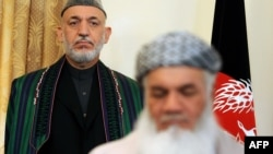 Water and Energy Minister Mohammad Ismail Khan (front) signs a document as Afghan President Hamid Karzai looks on at the presidential palace in Kabul in 2010.