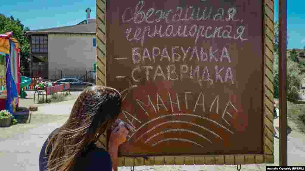 Kafe işçisi yalıda haber tahtasındaki yazılarnı yañarta