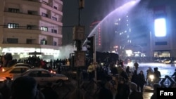 In Tehran, a water canon is used in Ferdowsi Square in an attempt to disperse demonstrators on December 31.