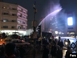 Authorities try to disperse demonstrators by using a water cannon in Ferdowsi Square on December 31.