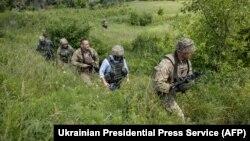 Президент України Володимир Зеленський (на фото в голубій сорочці) під час поїздки до лінії фронту на Луганщині, 27 травня 2019 року