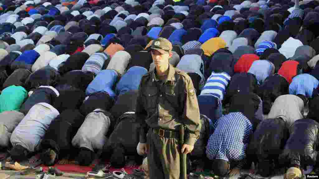 A Russian Interior Ministry member stands guard while Muslims pray to celebrate Eid al-Fitr in Moscow.