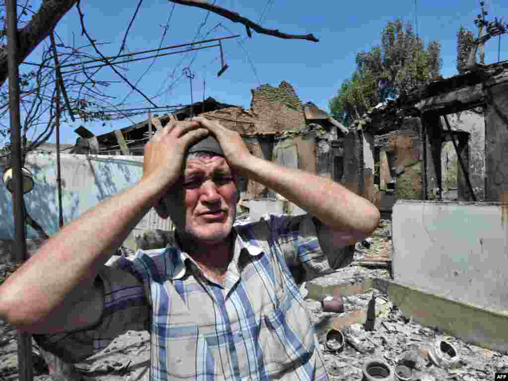 An ethnik Uzbek stands beside the wreckage of his burned-out home in Osh on June 14.