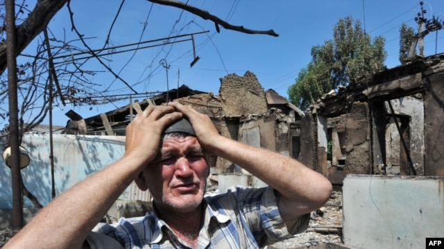 An ethnic Uzbek man stands beside the wreckage of his burned-out home in Osh on June 14, 2010.