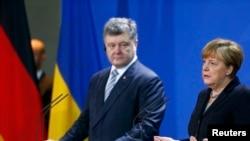 Президент України Петро Порошенко (в центрі) під час прес-конференції з канцлером Німеччини Анґелою Меркель, Берлін, 1 лютого 2016 року