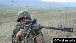 A Karabakh Armenian soldier practices sniper fire during a military exercise.