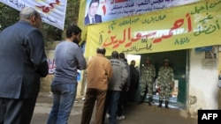 Soldiers stand guard as voters line up at a polling station in the Manial neighbourhood of Cairo.