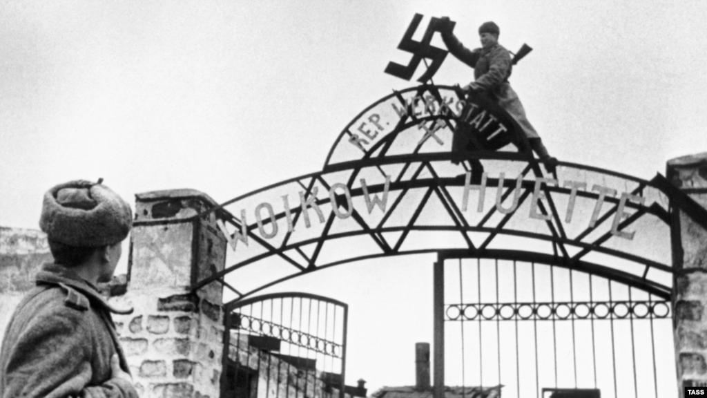 Денацифікація почалася з очищення Криму від символів окупації ще до Нюрнберзького трибуналу. На фото: радянські солдати знімають свастику з воріт заводу в Керчі, листопад 1943 року