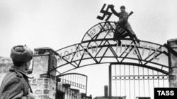 Советские солдаты снимают свастику с ворот завода в Керчи, ноябрь 1943 года