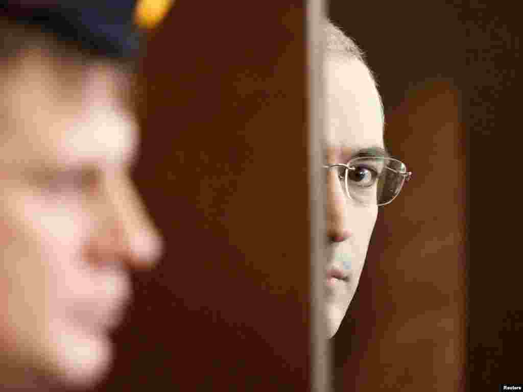 Looking out of the defendant's cage as he attends a court session in Moscow on October 19, 2010.