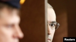 Russia -- Mikhail Khodorkovsky (R) looks out of the defendant's cage as he attends a court session in Moscow, 19Oct2010