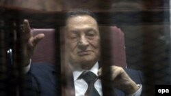 Hosni Mubarak waves from defendants' cage at a courtroom during his trial in Cairo, April 29, 2015